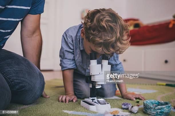little boy using microscope. - neugierde stock-fotos und bilder