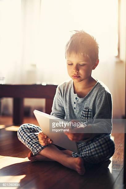 Little boy using modern tablet on the floor