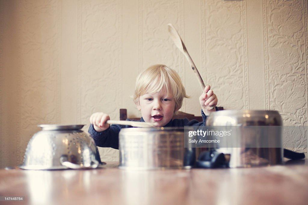 Little boy using saucepans as drums : Stock Photo