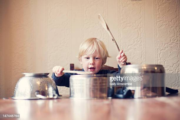 little boy using saucepans as drums - stahlfass stock-fotos und bilder