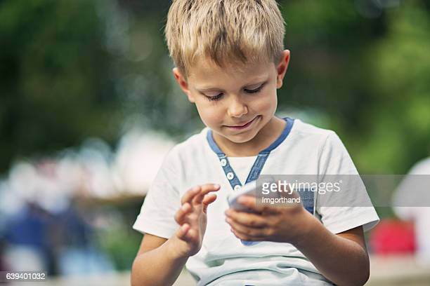 Little boy using smartphone in the park