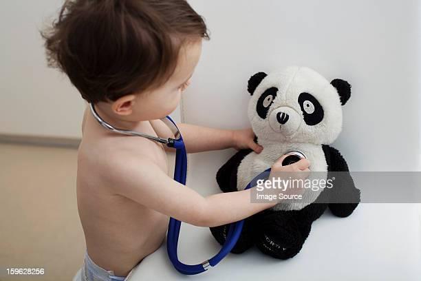 Little boy using stethoscope on panda toy
