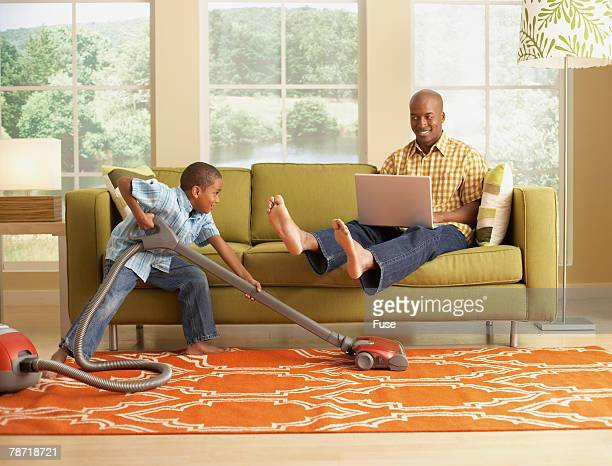 little boy vacuuming beneath his father's feet - black male feet stock photos and pictures