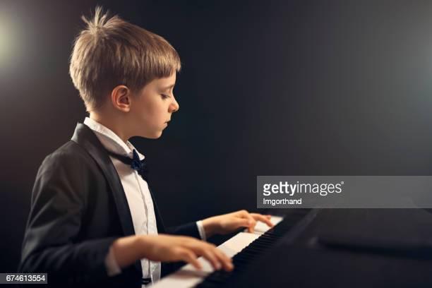 Little boy virtuoso performing piano concerto