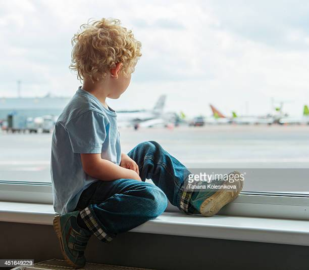 Little boy waiting for his flight in airport