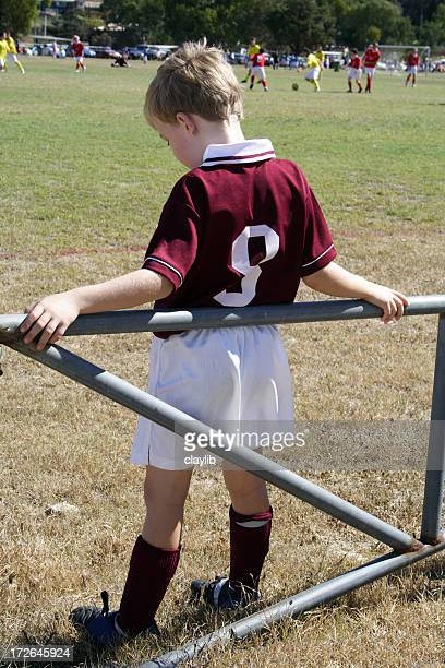 Little boy waiting in reserve to play in soccer game