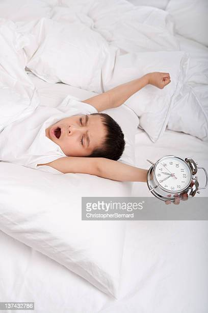 Little boy waking up stretching in bed