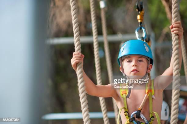 Kleinen Jungen zu Fuß auf einer Seilbrücke