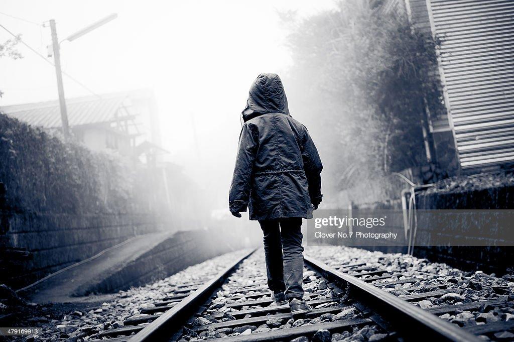 Little boy walking on train tracks : Stock Photo