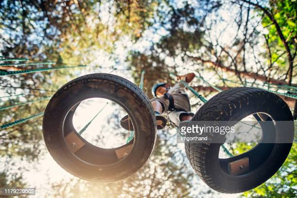 little boy walking on tyres at the ropes course - low stock pictures, royalty-free photos & images