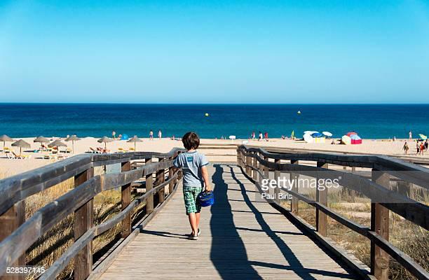 Little boy walking toward the ocean