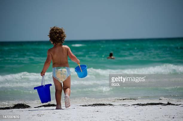 Little boy walking towards sea