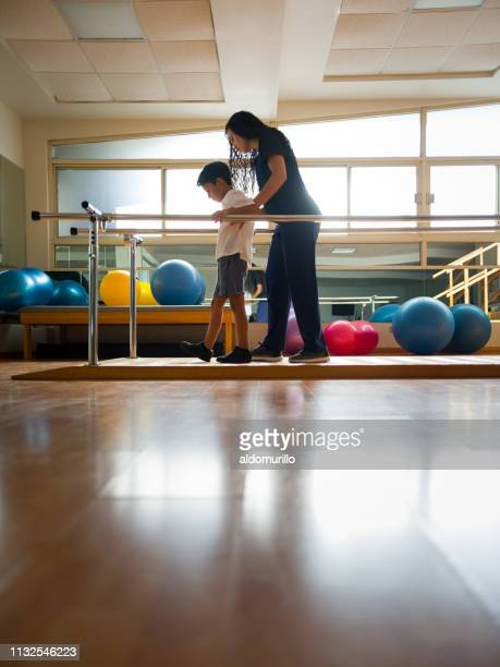little boy walking with help from physical therapist - physical therapy stock pictures, royalty-free photos & images