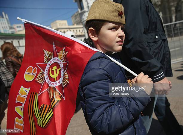 A little boy walks holding a flag and wearing a historical cap like those warn by Soviet Red Army soldiers during World War II ahead of celebrations...