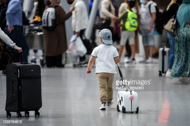 Little boy walks with his suitcase past travellers queing at the check-in counter on July 2, 2021 at the airport of Duesseldorf as summer holidays...