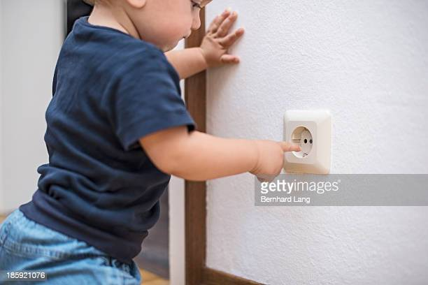 Little boy (1 y) wants to touch plug socket