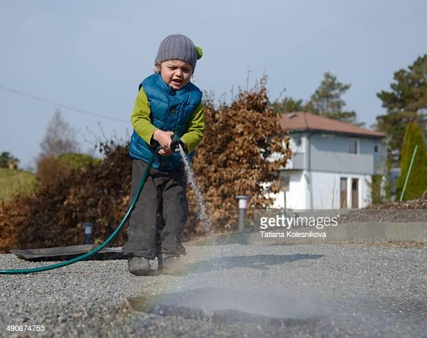 little boy washing car mats in the yard - estera fotografías e imágenes de stock
