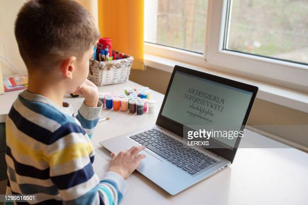 little boy watching a video tutorial on his laptop - microsoft stock pictures, royalty-free photos & images