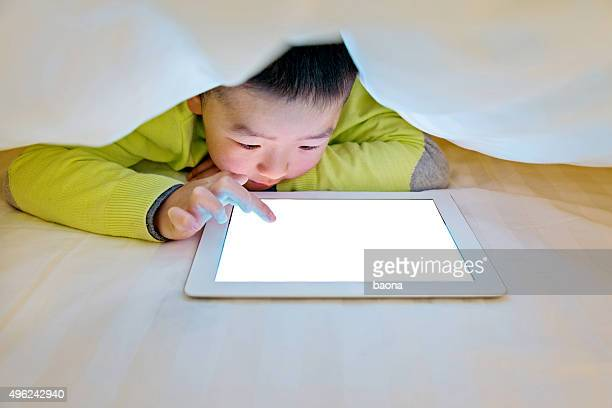 Little boy watching digital tablet in bed