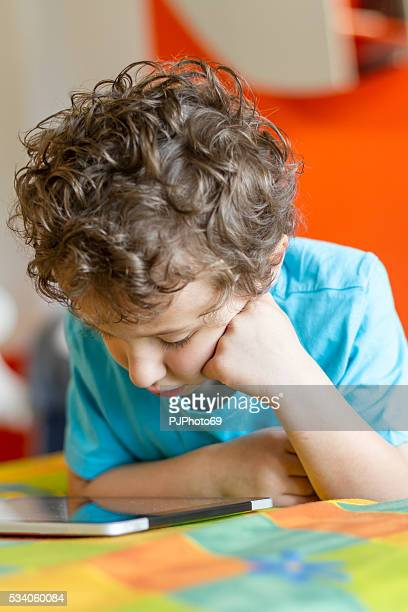 little boy watching digital tablet - pjphoto69 stock pictures, royalty-free photos & images
