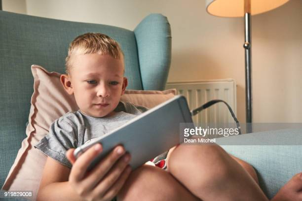 Little boy watching online videos on mobile phone