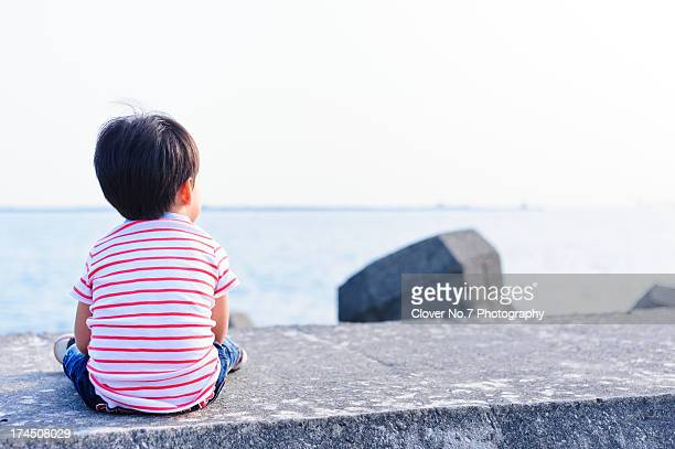 Little boy watching the sea.