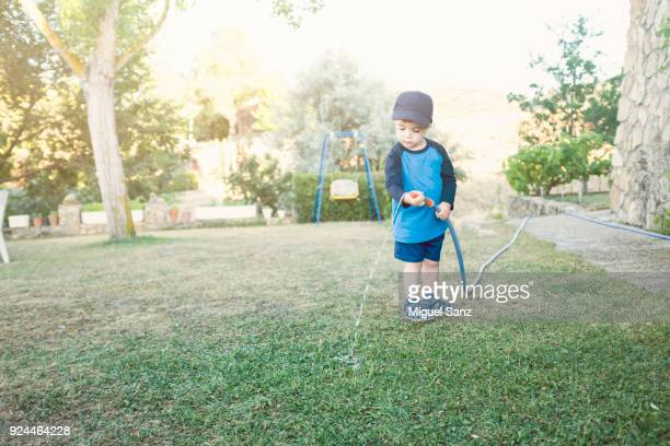 Little boy watering  the lawn with a garden hose