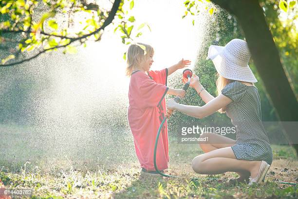 Little boy watering with his mother in garden
