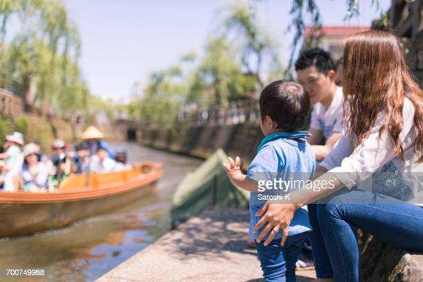 Little boy waving hand to people on boat
