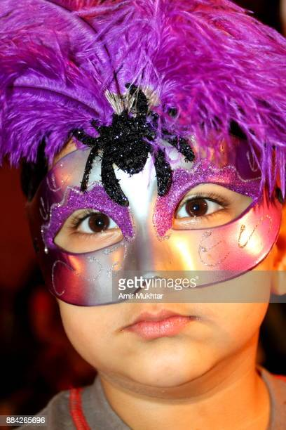little boy wearing a colorful mask - amir mukhtar stock photos and pictures