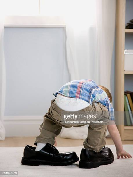 little boy wearing a man's shoes