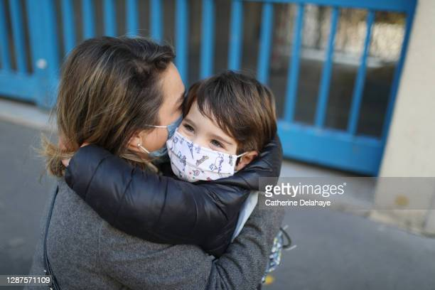 a little boy wearing a protective face mask, embracing his mother in front of school - education stock pictures, royalty-free photos & images