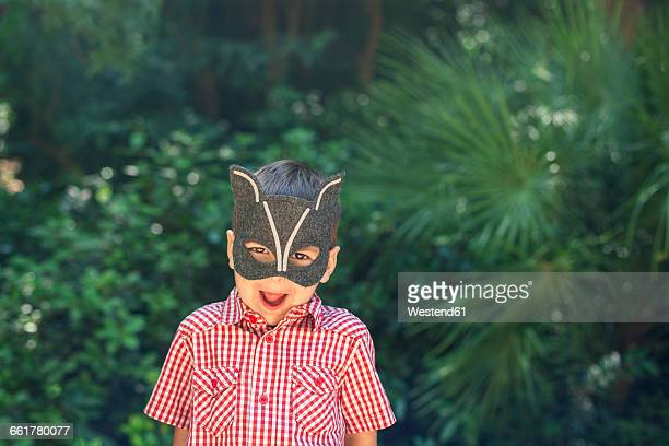 Little boy wearing animal mask pulling funny faces