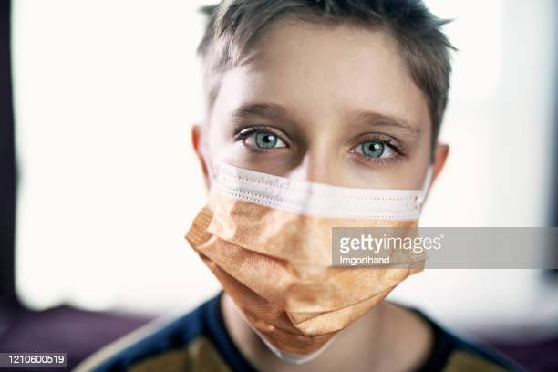 little boy wearing anti virus mask staying at home - respirator mask stock pictures, royalty-free photos & images