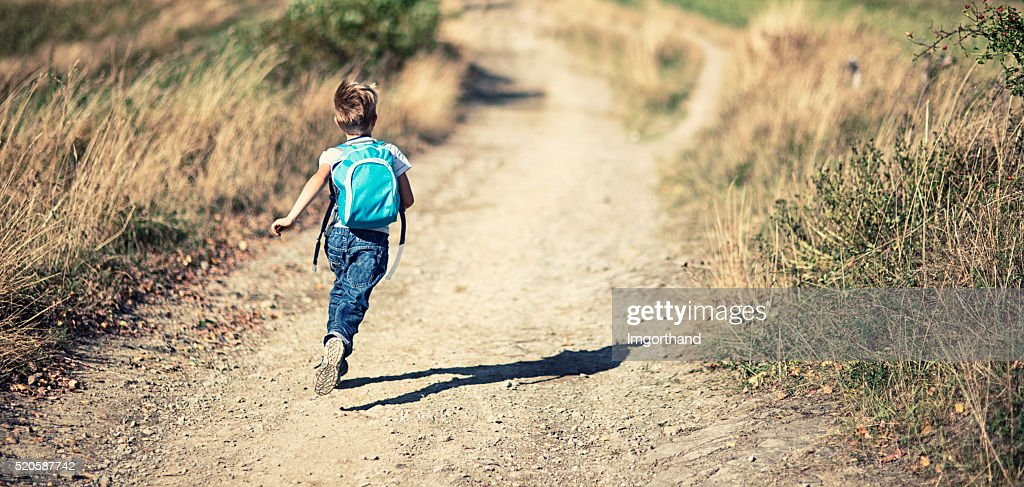 Little boy wearing backpack running on a dirt road : Stock Photo