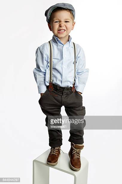 little boy wearing cap and suspenders pouting mouth - サスペンダー ストックフォトと画像