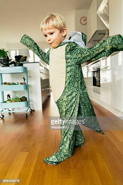 Little boy wearing dinosaur costume dancing