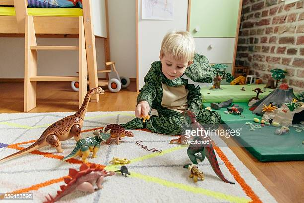 little boy wearing dinosaur costume playing with toy dinosaurs - nur kinder stock-fotos und bilder