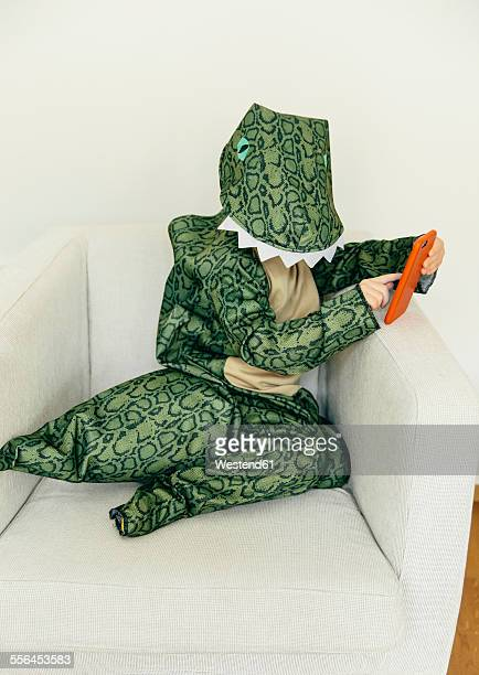 Little boy wearing dinosaur costume sitting on the couch with smartphone