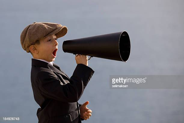 Little Boy Wearing Flat Cap Shouting On Old Fashioned Megaphone