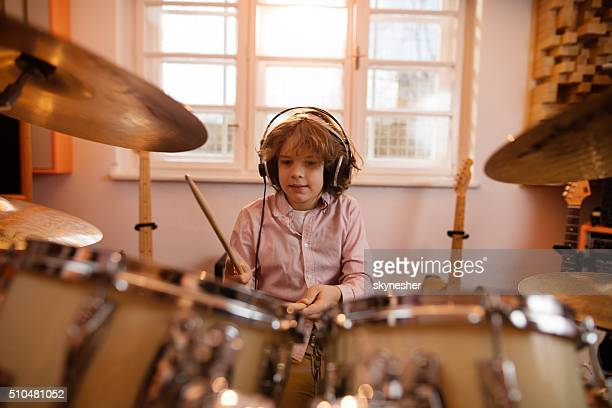 Little boy wearing headphones and playing drums.