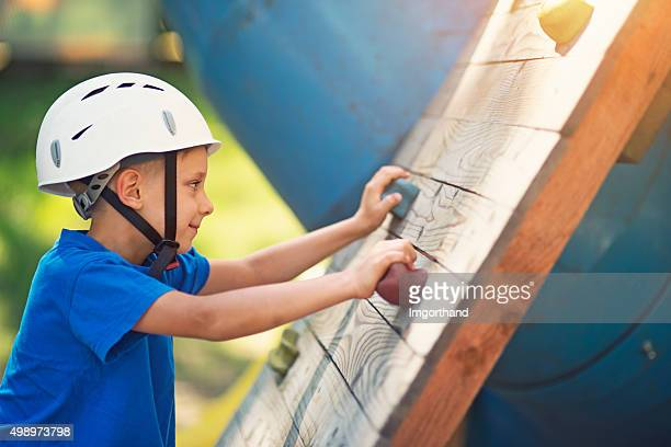 Kleiner Junge mit Helm zum Klettern auf Kletterwand