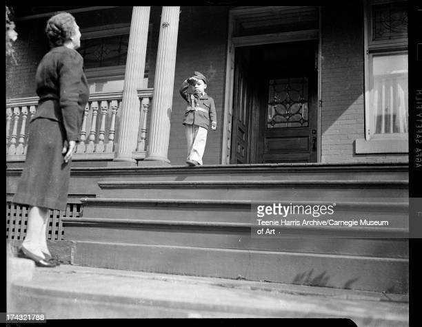 Little boy wearing military uniform standing at top of stairs of porch of brick house with woman standing at bottom Pittsburgh Pennsylvania c 1944