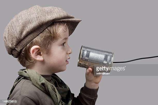 Little Boy Wearing Newsboy tapa hablando por teléfono de lata