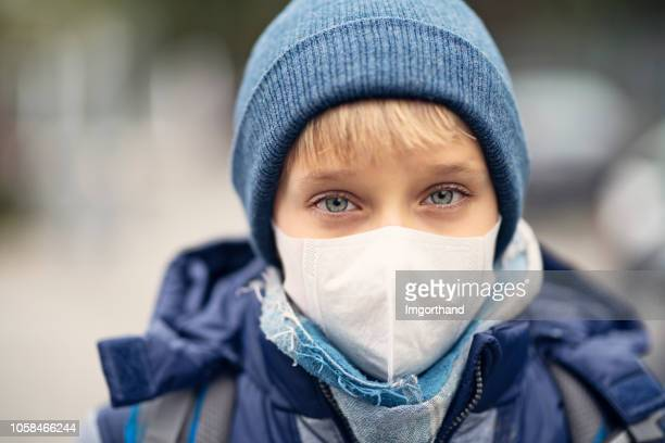 little boy wearing pollution mask going to school - smog stock pictures, royalty-free photos & images