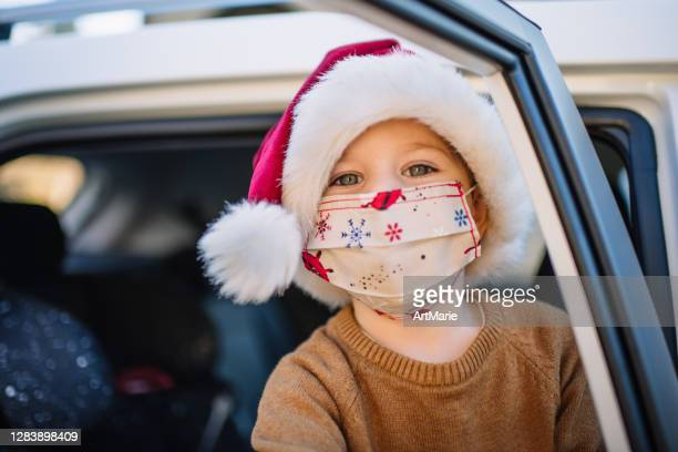 little boy wearing protective face mask and santa hat in car on christmas - coronavirus winter stock pictures, royalty-free photos & images