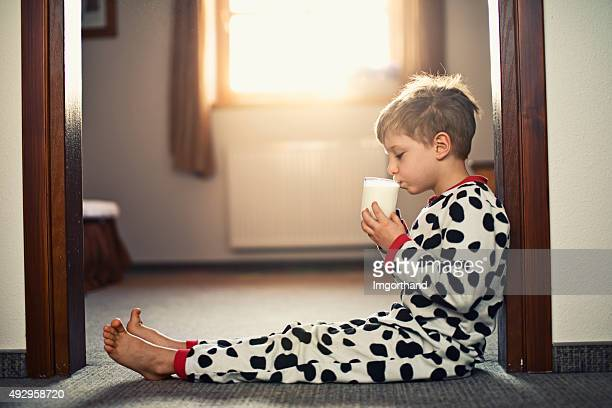 Little boy wearing pyjamas drinking glass of milk in morning