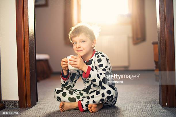Little boy wearing pyjamas drinking morning glass of milk.