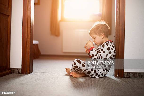 Little boy wearing pyjamas drinking morning glass of water.