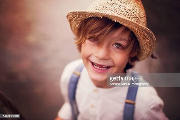 Little boy wearing straw hat standing in creek